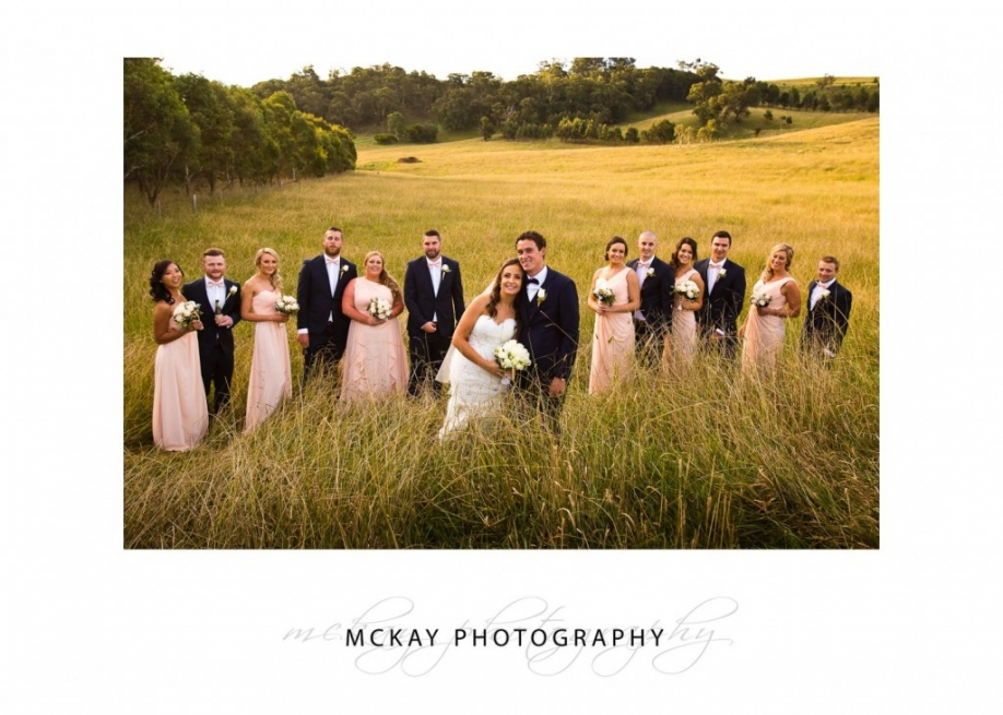 Bridal party photo in long grass at Bendooley Estate Bowral