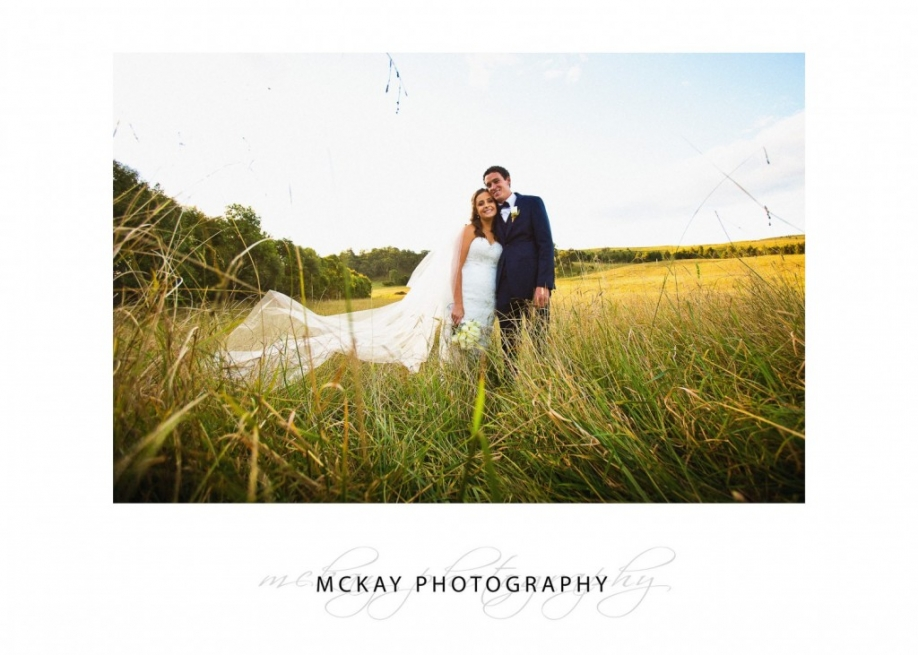Bride & groom in long grass Bendooley Estate wedding