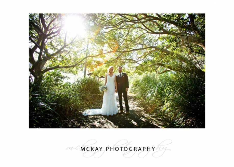 Bride and groom under tree light backlit