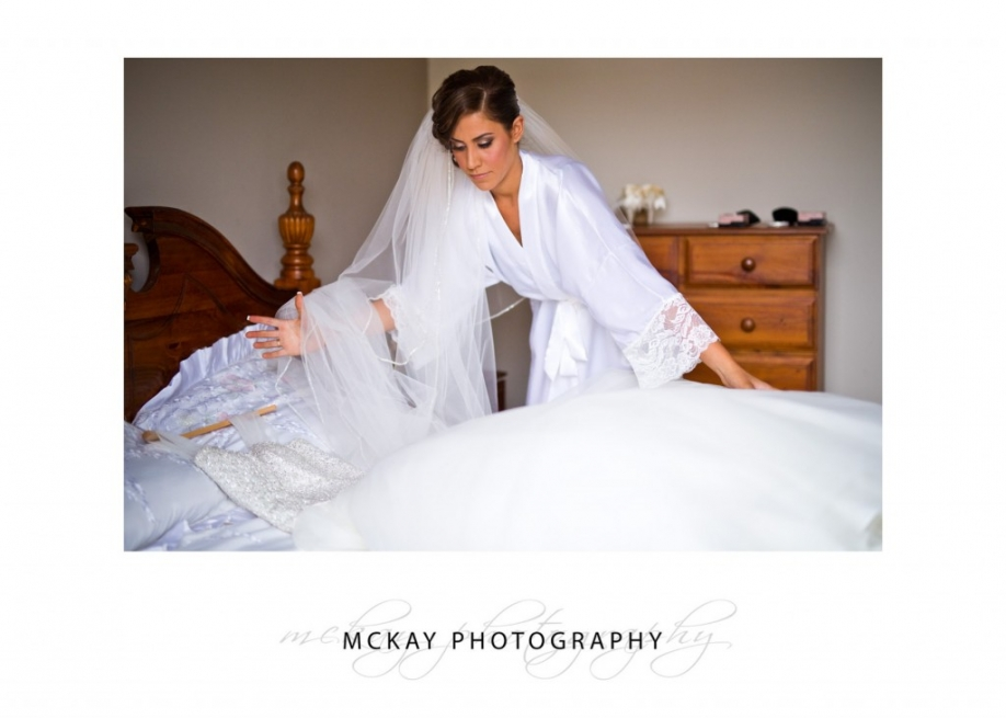 Mary lays her wedding dress on bed
