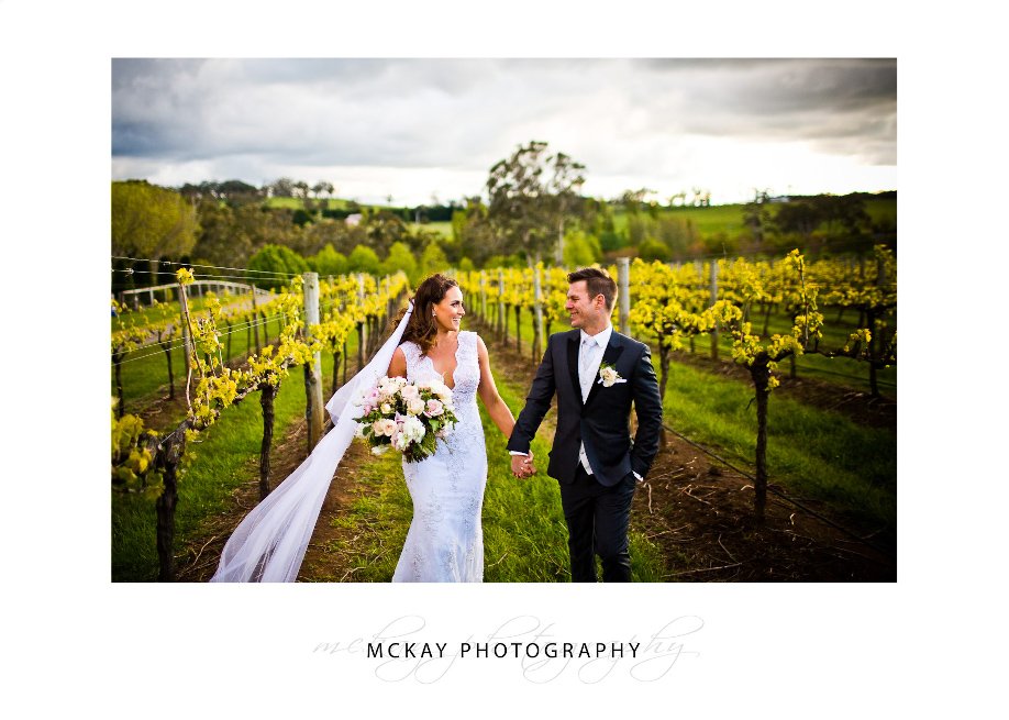 Kayleigh and Josh walk through vine rows at Centennial Vineyards wedding Bowrala