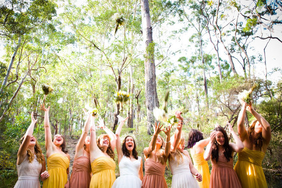 bridesmaids throwing flowers candid wedding photography