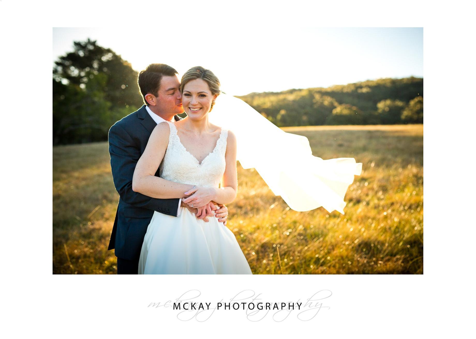 Bride groom grass field Bowral wedding photo sunset