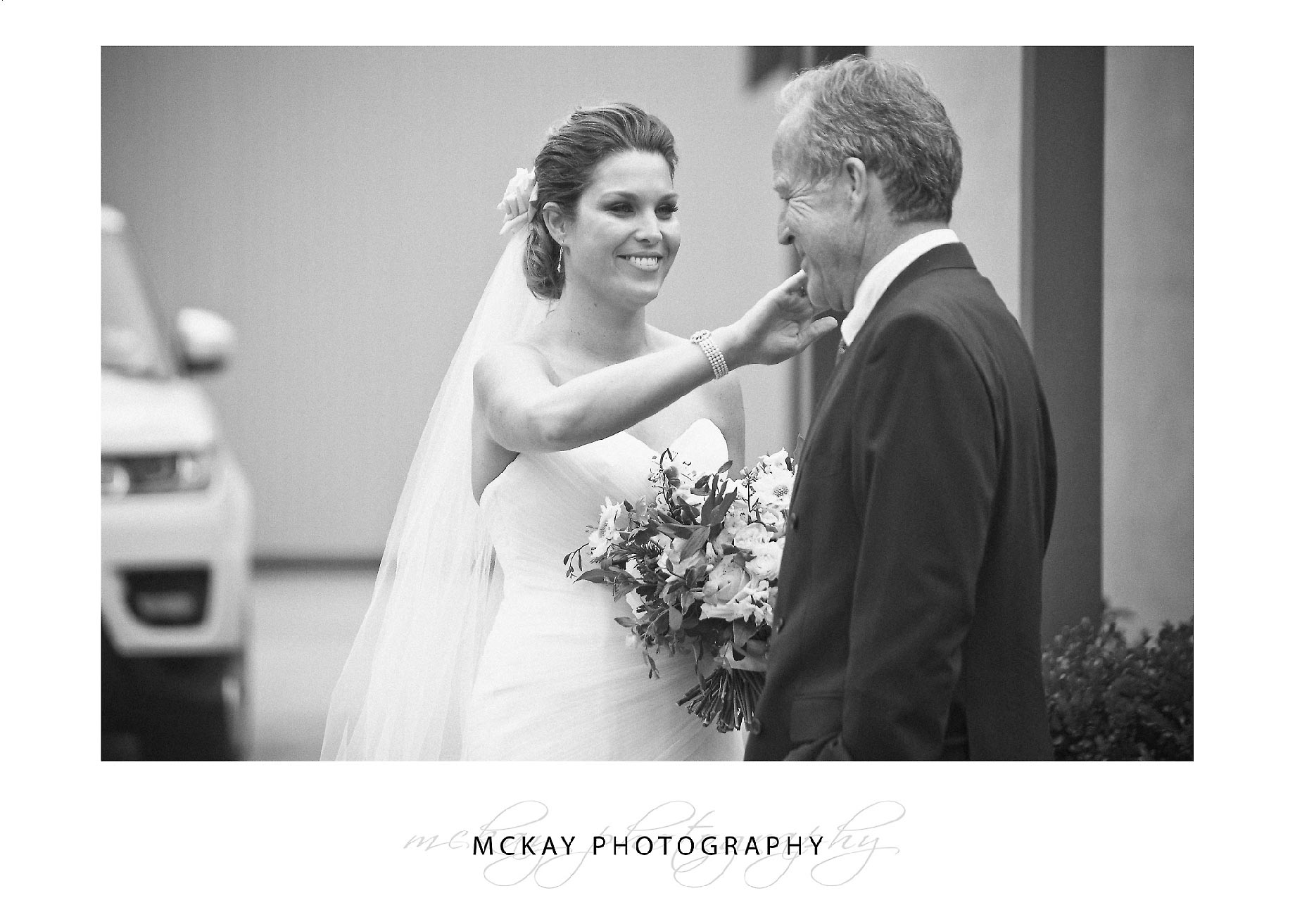 Bride wiping tear from Fathers eye before ceremony